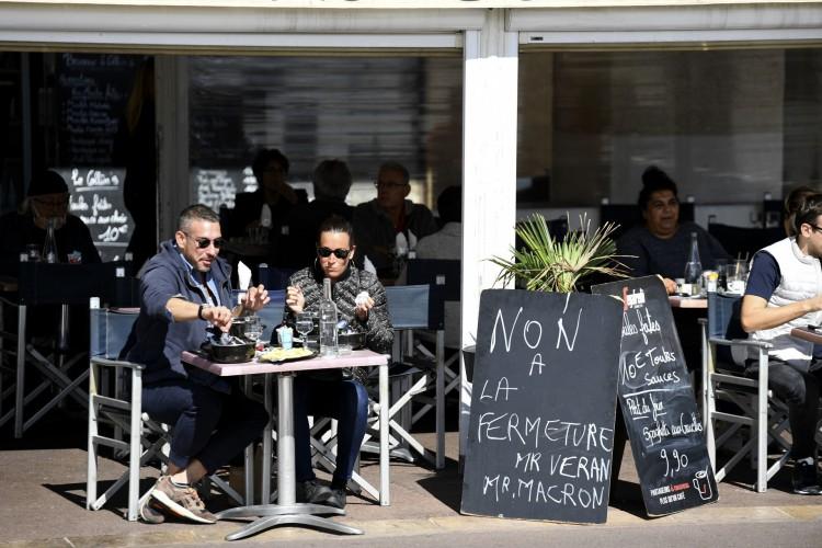 Duas pessoas almoçam no terraço de um restaurante ao lado de uma placa onde se lê