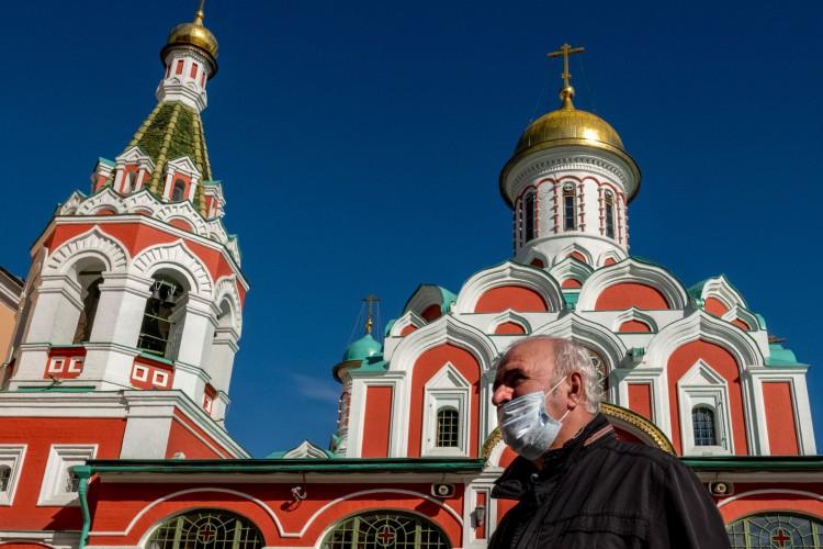 Um homem usando uma máscara facial para se proteger contra a doença do coronavírus passa por uma catedral ortodoxa russa na Praça Vermelha, no centro de Moscou, em 2 de outubro de 2020 (Foto: AFP)