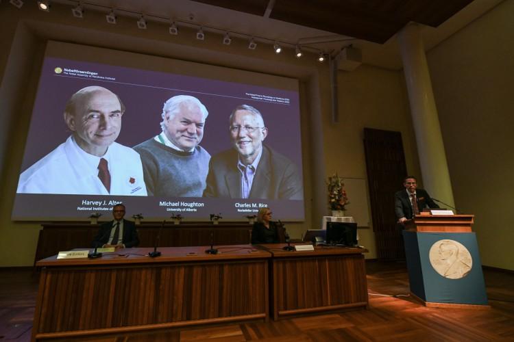 Thomas Perlmann (à direita), secretário do comitê do Prêmio Nobel, fala sobre os vencedores de 2020 do Nobel de Medicina, em destaque na tela:  Harvey Alter, Michael Houghton e Charles Rice (Foto: Jonathan NACKSTRAND / AFP)