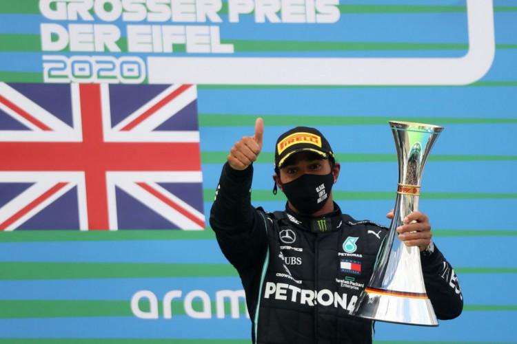 Lewis Hamilton comemora com um troféu no pódio após vencer a corrida do Grande Prêmio de Fórmula 1 e iguala recorde de 91 vitórias de Michael Schumacher (Foto: WOLFGANG RATTAY/Reuters)