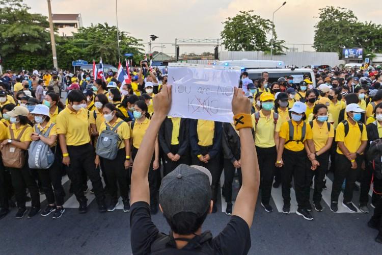 Manifestante pró-democracia segura uma placa para apoiadores monarquistas durante um comício antigovernamental em Bangkok, na Tailândia, em 14 de outubro de 2020 (Foto: AFP)