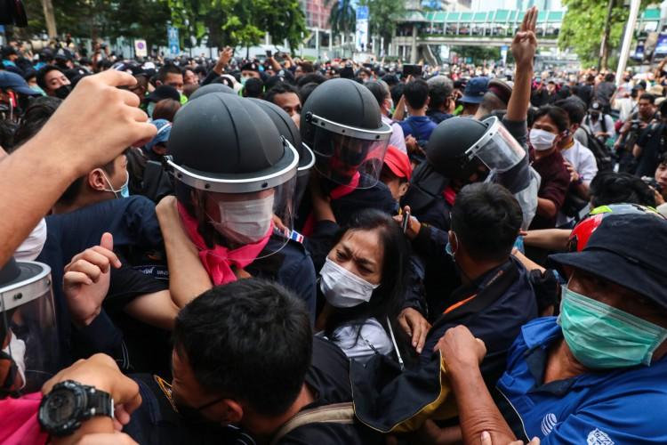 Manifestantes pró-democracia brigam com a polícia enquanto outro faz a saudação de três dedos em Bangcoc em 15 de outubro de 2020, depois que a Tailândia emitiu um decreto de emergência após um comício antigovernamental no dia anterior.(Foto: TAYLOR / AFP) (Foto: TAYLOR / AFP)