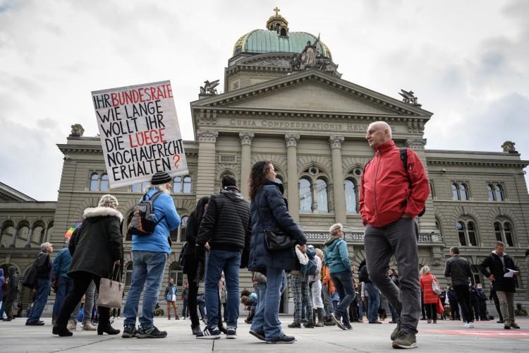 Um homem segura um cartaz em que se lê em alemão