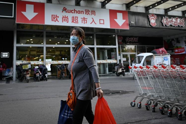 Mulher caminhando em um supermercado de Pequim, na China (Foto: AFP)
