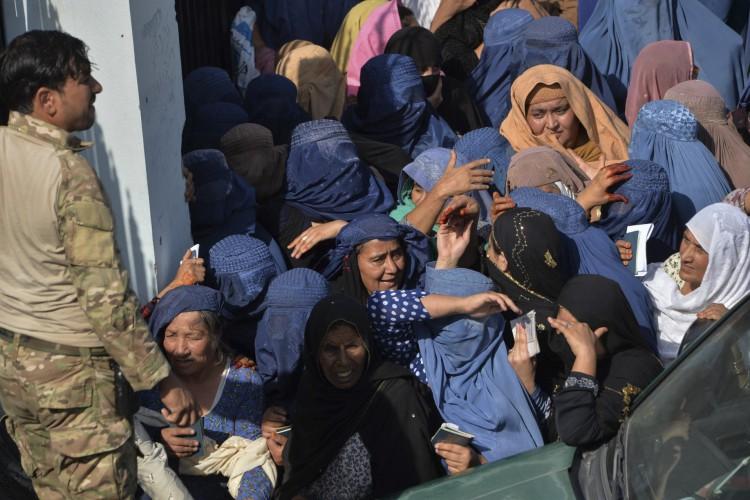 Mulheres se reúnem do lado de fora do portão de entrada principal de um estádio de futebol após a morte de pelo menos 11 mulheres quando as pessoas estavam solicitando vistos para o Paquistão, em Jalalabad em 21 de outubro de 2020 (Foto: AFP)