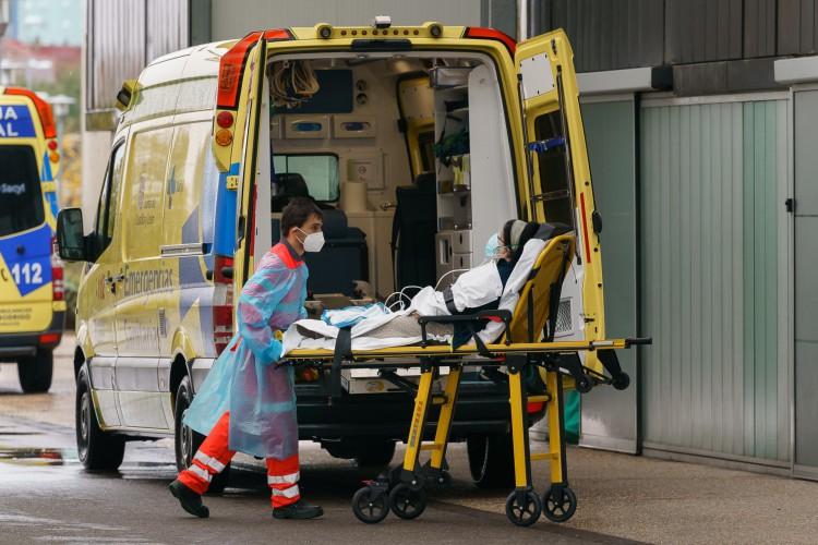Espanha, em 21 de outubro de 2020, um paramédico tira uma mulher de uma ambulância do lado de fora do Hospital Burgos em Burgos (Foto: Cesar Manso / AFP)