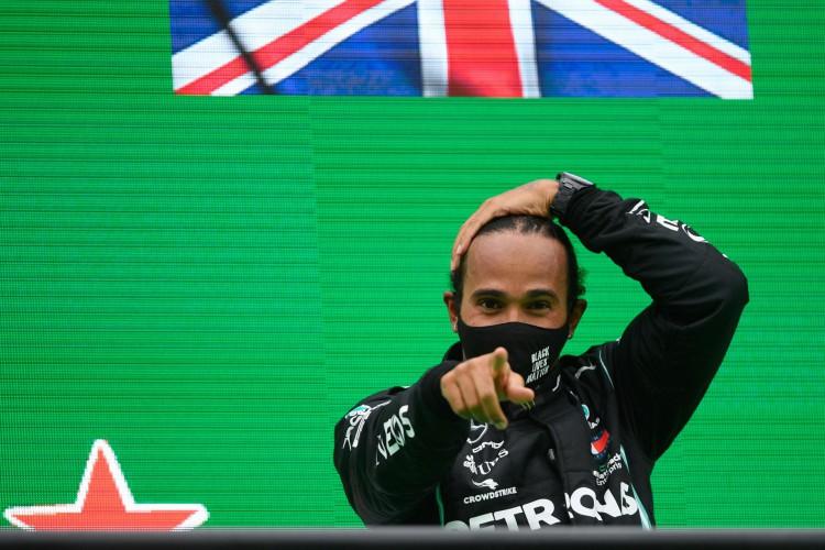 O piloto britânico da Mercedes, Lewis Hamilton, comemora no pódio após vencer o Grande Prêmio de Fórmula 1 de Portugal no Autódromo Internacional do Algarve no dia 25 de outubro de 2020 em Portimão. (Foto de RUDY CAREZZEVOLI / POOL / AFP) (Foto: RUDY CAREZZEVOLI / AFP)