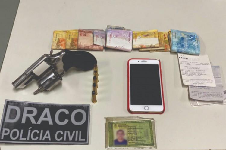 As equipes encontraram um revólver calibre 38 com cinco munições, mais de R$ 1.200,00 em espécie, celulares e comprovantes de depósitos no endereço do suspeito (Foto: Divulgação/Polícia Civil)