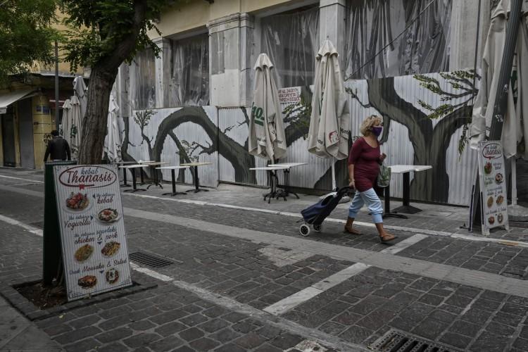 Uma mulher passa por um restaurante tradicional de kebab fechado no centro de Atenas enquanto cafés, bares e restaurantes estão fechados devido ao bloqueio parcial para conter a disseminação do novo coronavírus (Foto: AFP)