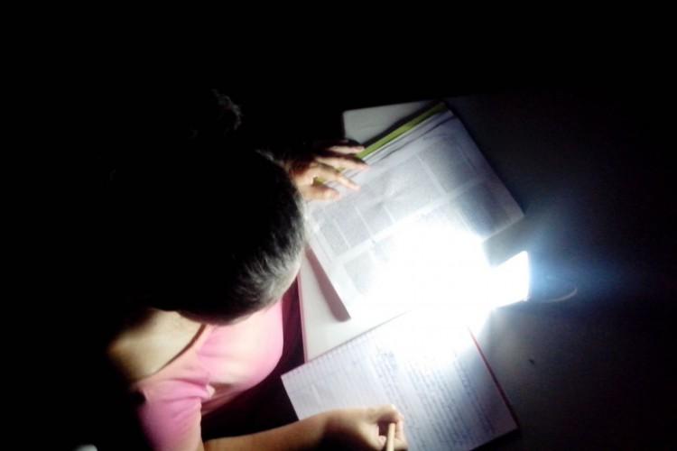 Ducilvânia Costa, moradora de Macapá, estudando em casa com o auxílio de uma lâmpada de emergência durante o apagão sofrido pelo estado.  (Foto: Ricardo Costa/Acervo Pessoal)