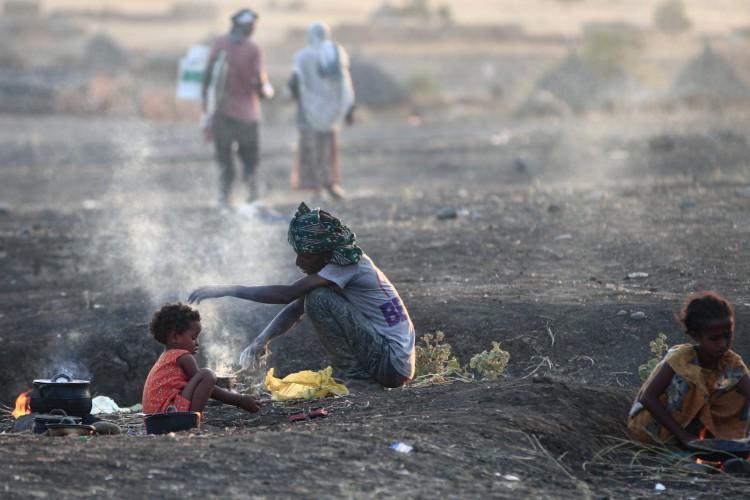 Refugiados etíopes que fugiram dos intensos combates em sua terra natal de Tigray, cozinham sua refeição no centro de recepção de fronteira de Hamdiyet, no estado sudanês oriental de Kasala, em 14 de novembro de 2020 (Foto: AFP)