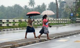 Mulheres caminham por uma estrada durante uma chuva de chuva enquanto o ciclone Nivar se aproxima, em Beruwala, a cerca de 58 km da capital do Sri Lanka      Caption