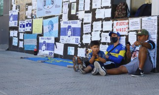 Fans of Argentine soccer great Diego Maradona sit next to a wall filled with encouraging messages outside the clinic where Maradona underwent brain surgery, in Olivos, on the outskirts of Buenos Aires, Argentina November 5, 2020. REUTERS/Matias Baglietto