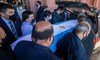 Foto da apostila divulgada pela assessoria de imprensa da Presidência da Argentina mostrando o caixão da falecida lenda do futebol argentino Diego Armando Maradona sendo colocado no carro funerário, em frente à casa do governo Casa Rosada, em Buenos Aires, em 26 de novembro de 2020. - Diego Maradona será sepultado quinta-feira nos arredores de Buenos Aires, disse um porta-voz. Maradona, que morreu de ataque cardíaco na quarta-feira aos 60 anos, será enterrado no cemitério Jardin de Paz, onde seus pais também foram enterrados, disse Sebastian Sanchi à AFP. (Foto: ESTEBAN COLLAZO / Assessoria de Imprensa da Presidência da Argentina / AFP)