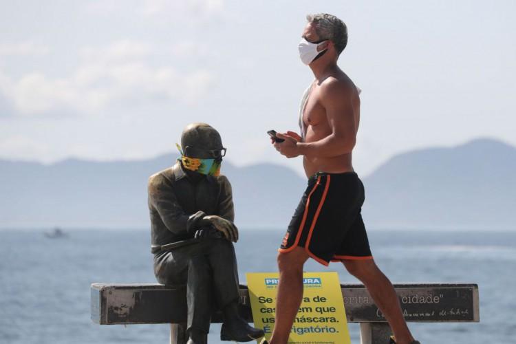 Um homem caminha ao lado da estátua do escritor brasileiro Carlos Drummond de Andrade que usa máscara protetora no primeiro dia de uso obrigatório de máscaras na cidade do Rio de Janeiro, em meio ao surto de doença por coronavírus (COVID-19), na praia de Copacabana (Foto: REUTERS / Sergio Moraes)