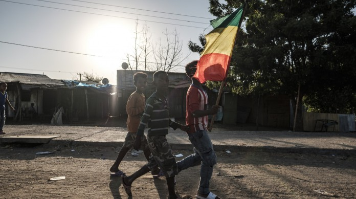 Grupo de meninos anda com a bandeira do Império da Etiópia, muito relacionada a um passado glorioso do país, na cidade de Mai Kadra, onde ocorreu massacre no início de novembro