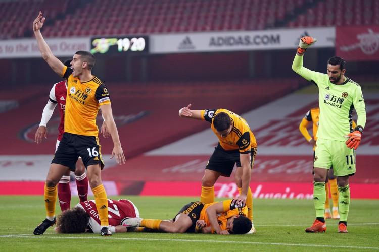 Jogadores esboçam preocupação após Raúl Jiménez sofrer pancada na cabeça na partida entre Arsenal e Wolverhampton (Foto: JOHN WALTON / AFP )