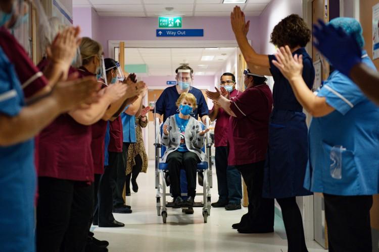 Margaret Keenan (C), 90, é aplaudida pela equipe após ela retornar e se tornar a primeira pessoa a receber a vacina da Pfizer-BioNtech Covid-19 na University Hospital in Coventry, central England (Foto: Jacob King / POOL / AFP)