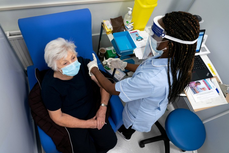 Londres, em 8 de dezembro de 2020. Anne Irene (esquerda) reage ao receber uma dose da vacina Pfizer / BioNTech Covid-19 no Croydon University Hospital - A Grã-Bretanha em 8 de dezembro comemorou uma virada na luta contra a pandemia do coronavírus, ao iniciar o maior programa de vacinação da história do país com uma nova vacina contra Covid-19 (Foto: Dan CHARITY / AFP)