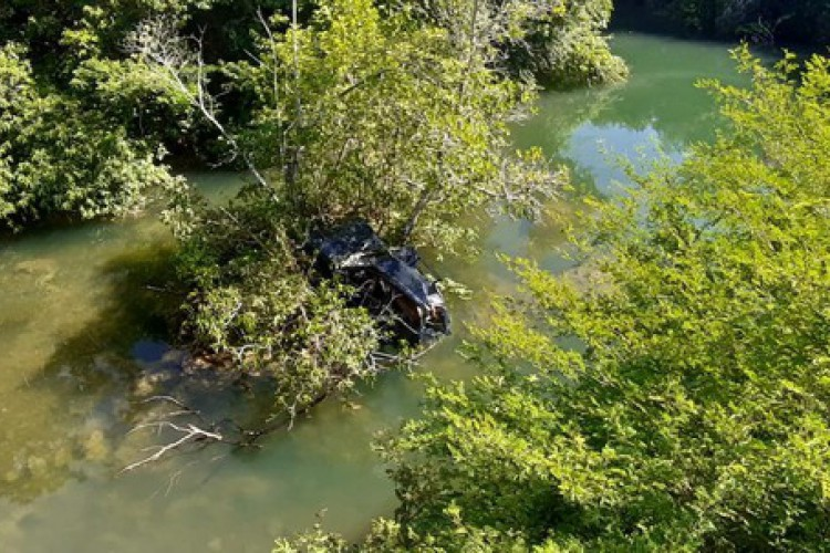 Após capotar, veículo ficou preso entre as árvores dentro do rio Betione, em Bodoquena (MS)    (Foto: 3° Pel PM Bodoquena)