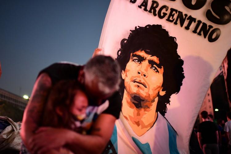 Um homem e sua filha, torcedores da lenda do futebol argentino Diego Maradona, choram ao se reunirem no Obelisco para prestar homenagem no dia de sua morte (Foto: AFP)