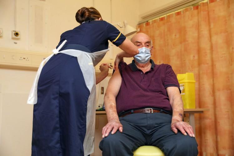 Brian Pinker, de 82 anos, foi o primeiro a receber dose da vacina da Oxford/AstraZeneca, aplicada pela enfermeira Sam-Foster (Foto: Steve-Parsons/AFP)