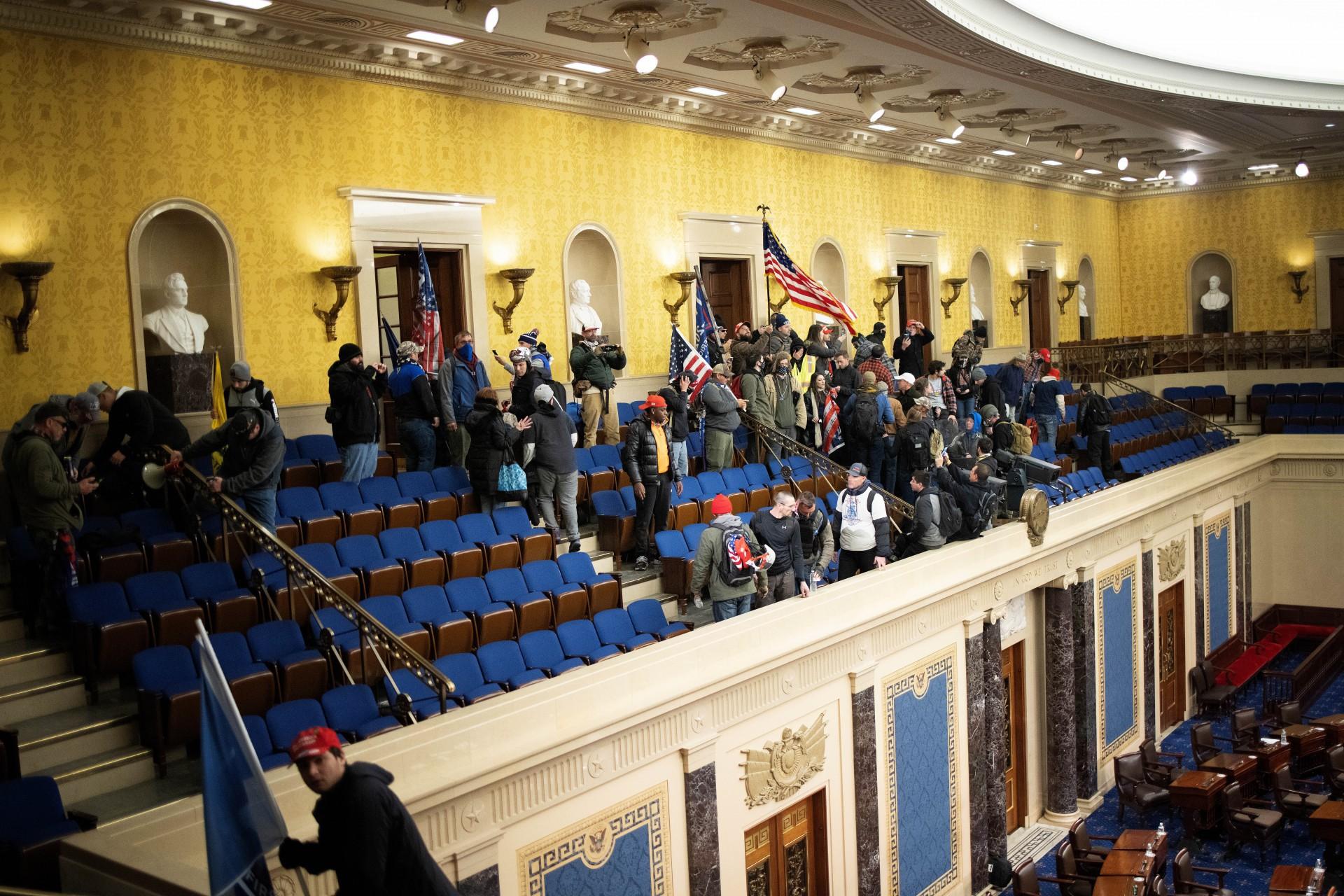 (Foto: WIN MCNAMEE / AFP)WASHINGTON, DC - 06 de janeiro: Uma multidão pró-Trump se reúne dentro da câmara do Senado no Capitólio dos EUA depois que grupos invadiram o prédio em 6 de janeiro de 2021 em Washington, DC. O Congresso realizou uma sessão conjunta hoje para ratificar a vitória do Colégio Eleitoral 306-232 do presidente eleito Joe Biden sobre o presidente Donald Trump. Um grupo de senadores republicanos disse que rejeitaria os votos do Colégio Eleitoral de vários estados, a menos que o Congresso designasse uma comissão para auditar os resultados das eleições. Win McNamee / Getty Images / AFP