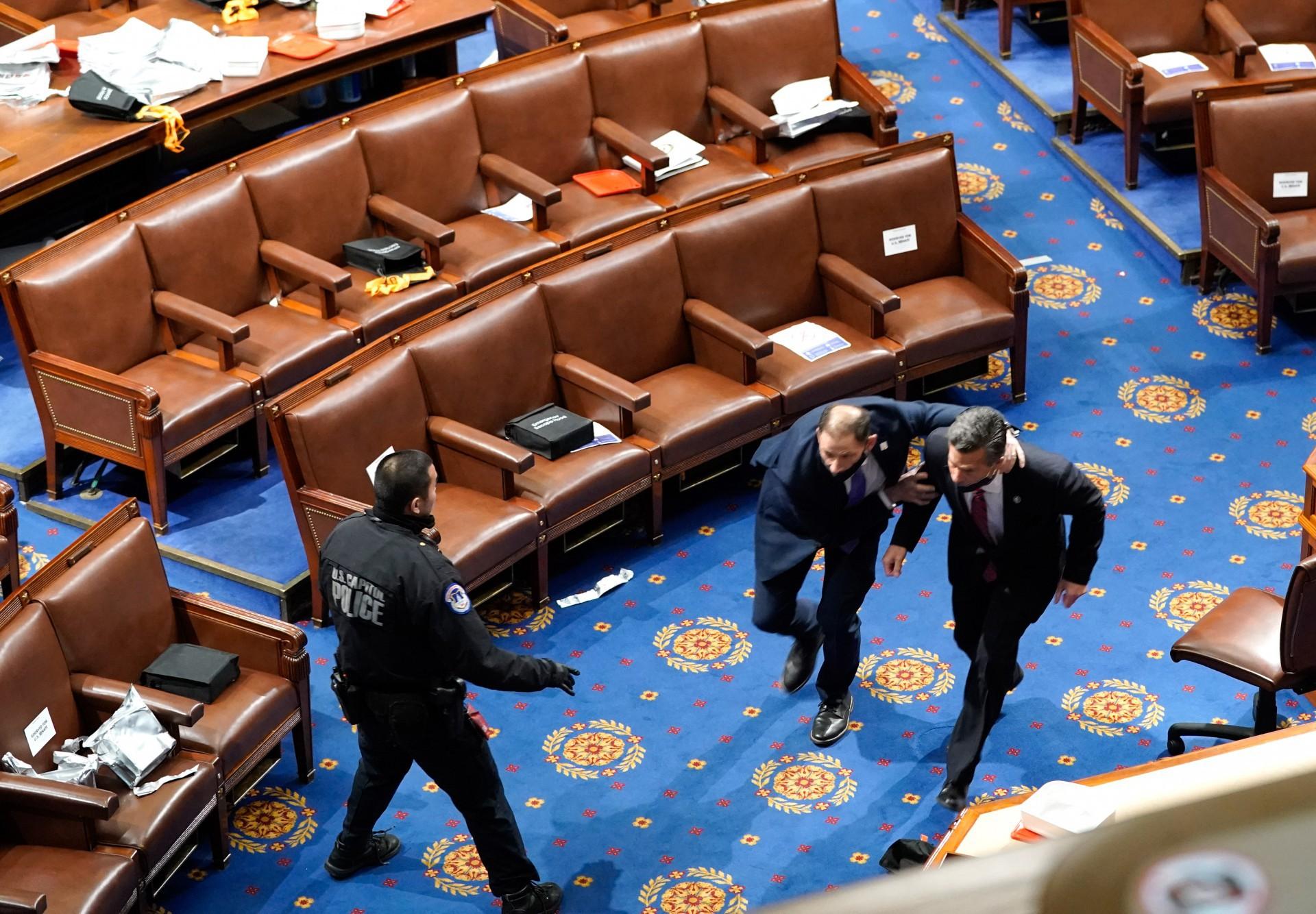 (Foto: Drew Angerer/AFP)WASHINGTON, DC - 06 de janeiro: Membros do Congresso concorrem para se esconder enquanto os manifestantes tentam entrar na Câmara da Câmara durante uma sessão conjunta do Congresso em 6 de janeiro de 2021 em Washington, DC O Congresso realizou uma sessão conjunta hoje para ratificar a vitória do Colégio Eleitoral 306-232 do presidente eleito Joe Biden sobre o presidente Donald Trump. Um grupo de senadores republicanos disse que rejeitaria os votos do Colégio Eleitoral de vários estados, a menos que o Congresso designasse uma comissão para auditar os resultados das eleições. Drew Angerer / Getty Images / AFP