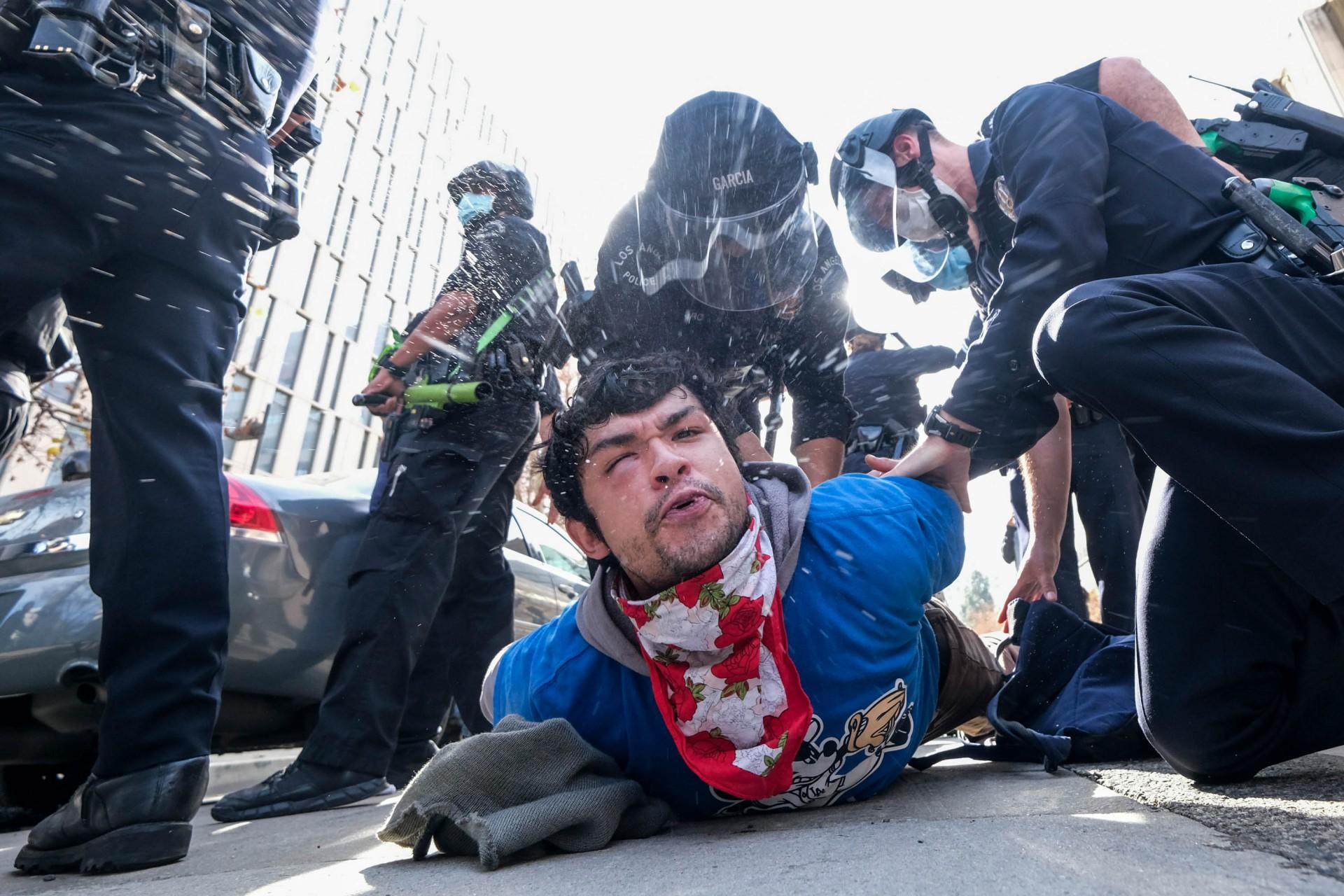 (Foto: RINGO CHIU / AFP)Um manifestante cospe enquanto é detido por policiais após uma briga estourada durante um protesto em apoio ao presidente dos EUA, Donald Trump, em Los Angeles em 6 de janeiro de 2021. - Os apoiadores de Trump, alimentados por suas afirmações espúrias de fraude eleitoral, estão protestando contra o esperado certificação da vitória de Joe Biden na Casa Branca pelo Congresso dos EUA em 6 de janeiro. (Foto: RINGO CHIU / AFP)