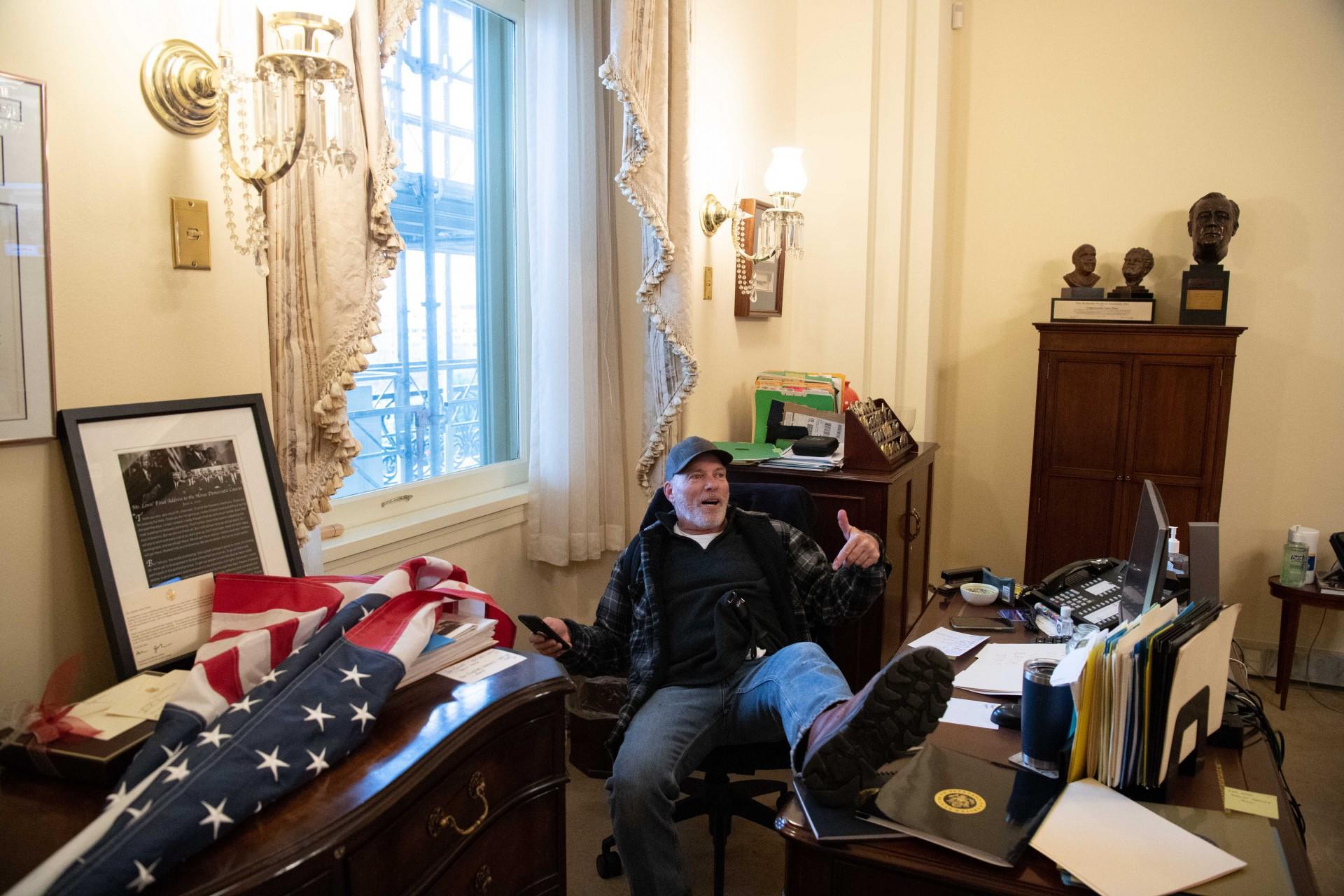 (Foto: SAUL LOEB / AFP)Um apoiador do presidente dos EUA, Donald Trump, está sentado no escritório da presidente da Câmara dos EUA, Nancy Pelosi, enquanto ele protesta dentro do Capitólio dos EUA em Washington, DC, 6 de janeiro de 2021. - Manifestantes violaram a segurança e entraram no Capitólio enquanto o Congresso debatia o a 2020 Certificação de Voto Eleitoral da eleição presidencial. (Foto de SAUL LOEB / AFP)