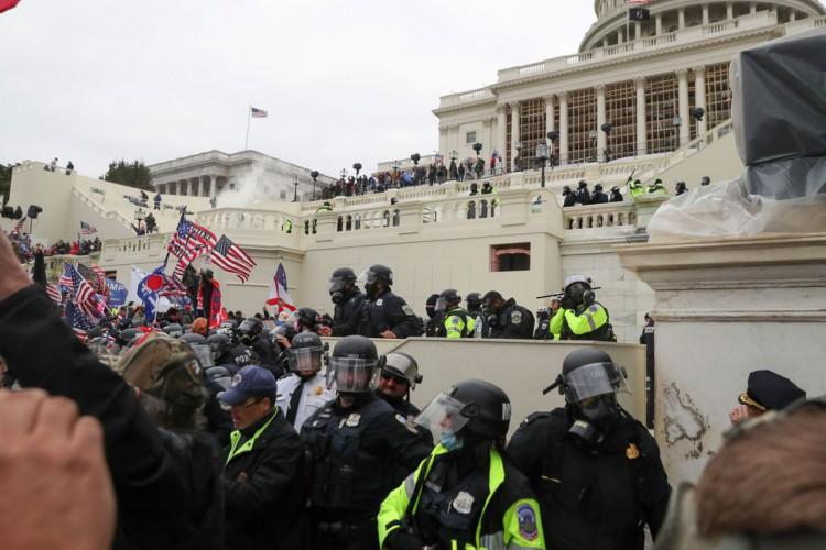 Policiais americanos montam guarda enquanto apoiadores do presidente norte-americano Donald Trumb protestam em frente ao Capitólio em Washington. (Foto: Leah Millis / Reuters / Direitos Reservados)