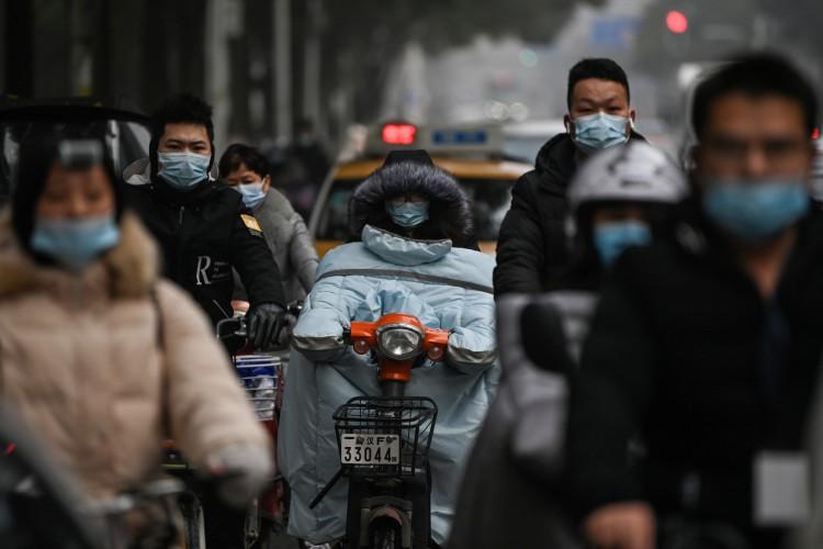 Pessoas em frente ao hotel onde membros da equipe da Organização Mundial da Saúde (OMS) faziam quarentena antes de começarem a investigar origem do novo coronavírus em Wuhan  (Foto: AFP)