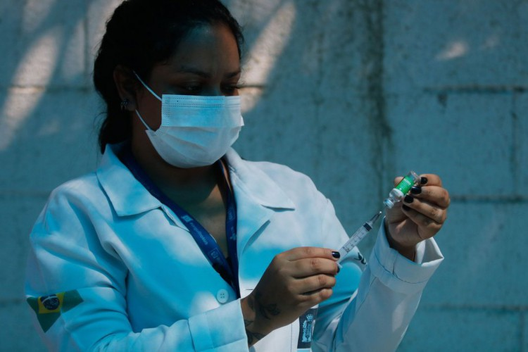 A técnica de enfermagem, Paula Roberta Moreira mostra a ampola da vacina contra a covid-19 antes de aplicar a injeção. Vacinação dos profissionais de saúde, veterinários e agentes funerários com 60 anos ou mais de idade, que estam na ativa, na Clínica da Família Estácio de Sá, na região central da cidade. O município do Rio de Janeiro ampliou hoje (27) o público-alvo da campanha de vacinação contra a covid-19. (Foto: Tânia Rêgo/Agência Brasil)