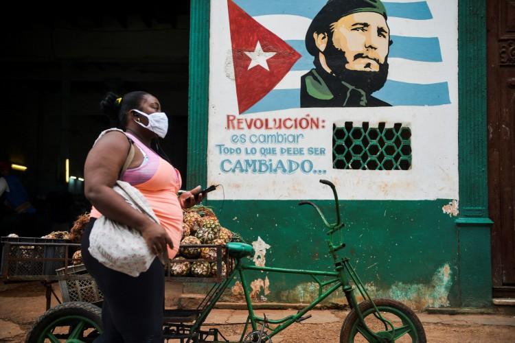 Uma mulher usando uma máscara facial caminha perto de um pôster retratando o falecido líder cubano Fidel Castro lendo