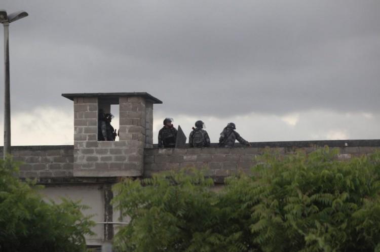 Movimentação de policiais militares do Ronda de Ações Intensivas e Ostensivas (Raio), no muro da Unidade Carrapicho em Caucaia, em 23 de maio de 2016