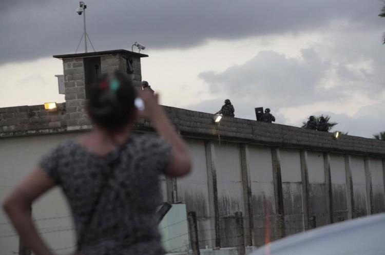 Mulher observa movimentação de policiais do Ronda de Ações Intensivas e Ostensivas (Raio), no muro da Unidade Prisional Desembargador Francisco Adalberto Barros de Oliveira Leal, conhecida como Carrapicho, em Caucaia, em 23 de maio de 2016