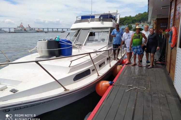 Foto da lancha Maestro e da tripulação, pouco antes de zarpar do Rio de Janeiro em direção ao Ceará. Na imagem, Wilson Santos aparece de chapéu, utilizando os acessórios descritos.  (Foto: ARQUIVO PESSOAL)