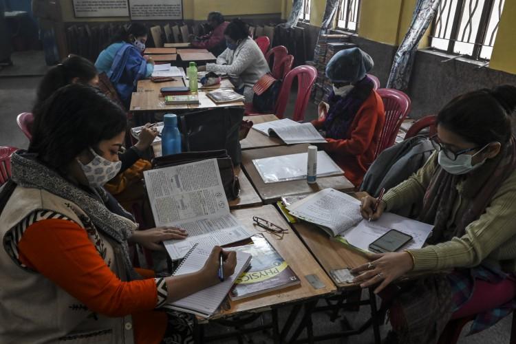 Os professores assistem a aulas online com seus telefones celulares enquanto o trabalho de higienização está em andamento em escola particular de Calcutá (Foto: AFP)