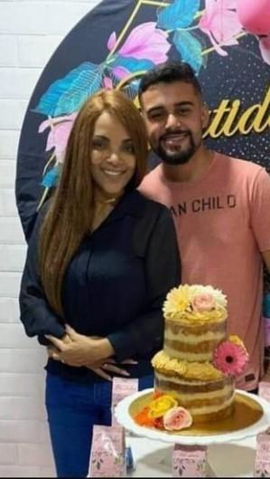 Flordelis e Allan Soares assumiram relação no aniversário de 60 anos da pastora e posaram ao lado do bolo (Foto: Reprodução/Redes sociais)