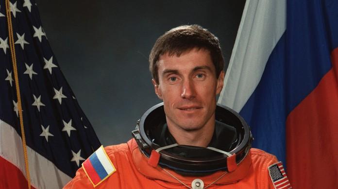 Krikalev com as bandeiras russa e estadunidense ao fundo, os países dos cosmonautas e dos astronautas
