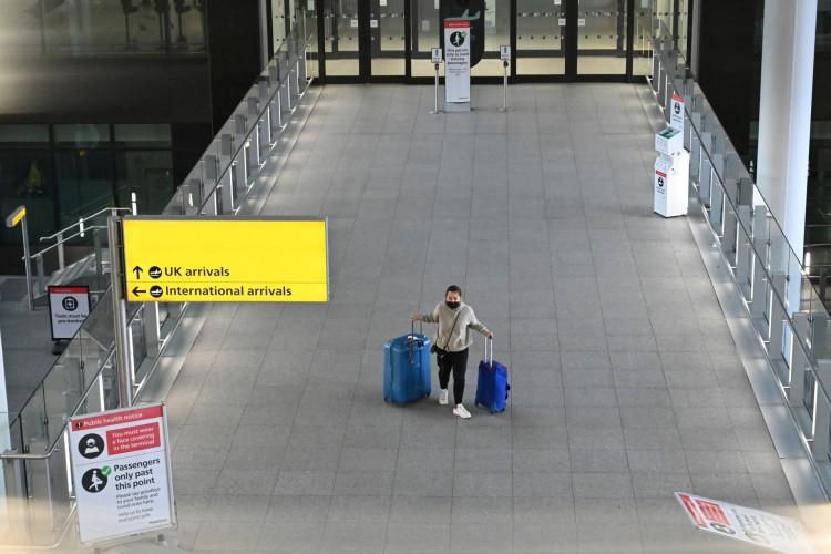 Um passageiro com bagagem é visto no Aeroporto Heathrow de Londres, no oeste de Londres, em 14 de fevereiro de 2021 (Foto: AFP)