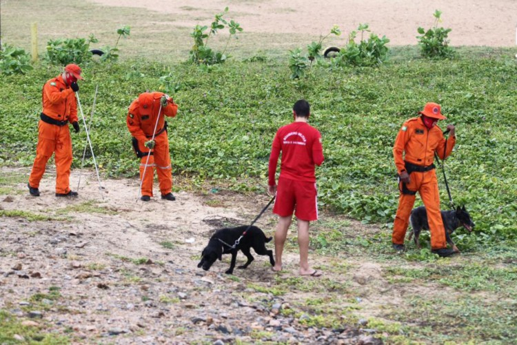 Homens do Corpo de Bombeiros usam cães farejadores para tentar localizar corpo de mulher que teria sido enterrado na região da Vila do Mar, após noite e madrugada violenta com registro de uma chacina (Foto: FÁBIO LIMA)