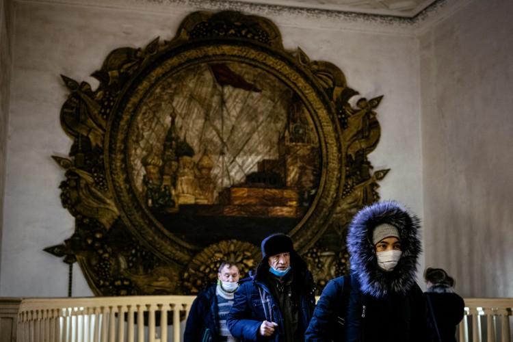 Pessoas com máscara deixando o Metrô de Moscou (Foto: AFP)