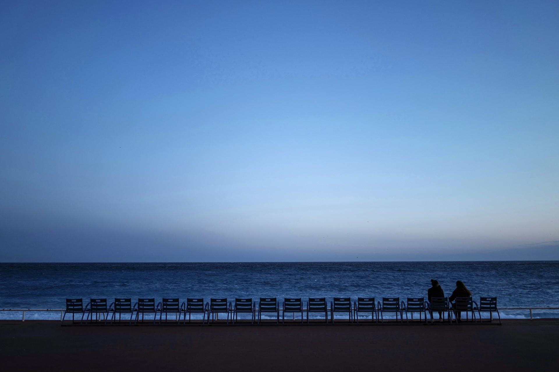Duas pessoas sentam-se em frente ao Mar Mediterrâneo no início da noite na