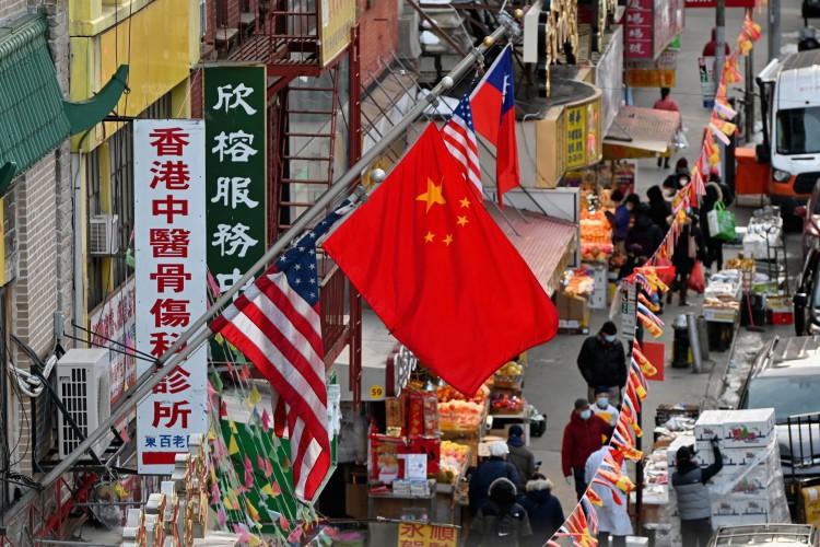 Bandeira chinesa está pendurada entre as bandeiras americanas em Chinatown em 17 de fevereiro de 2021 na cidade de Nova York     (Foto: Angela Weiss / AFP)