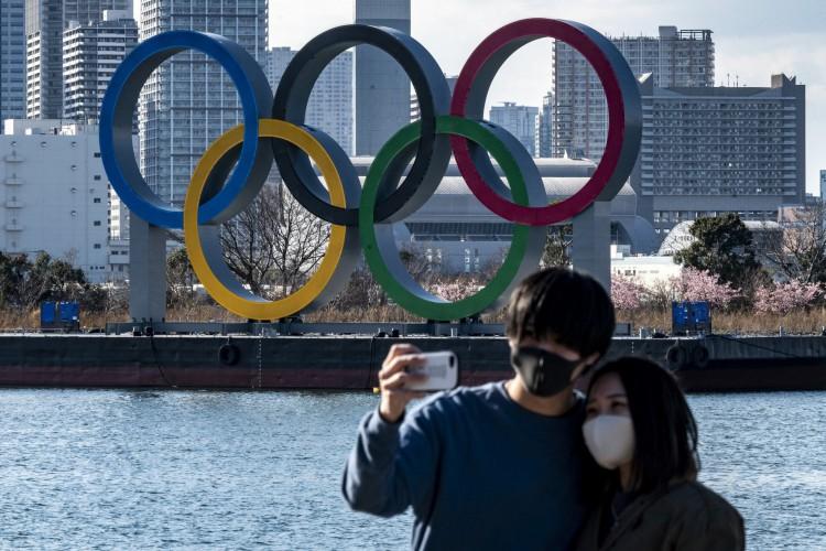 Casal posa para fotos em frente aos anéis olímpicos em exibição na orla Odaiba em Tóquio em 24 de fevereiro de 2021 (Foto: Philip FONG / AFP)