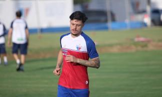 Meia Lucas Crispim corre em volta do campo em treino do Fortaleza no Centro de Excelência Alcides Santos, no Pici