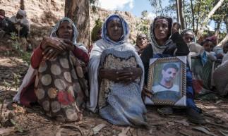 Pessoas lamentam as vítimas de um massacre supostamente perpetrado por soldados eritreus na aldeia de Dengolat, norte de Mekele, na Etiópia