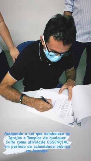 Prefeito Edilberto Beserra assinando lei que classifica atividades religiosas como essenciais em Acarape (Foto: Reprodução/Instagram)