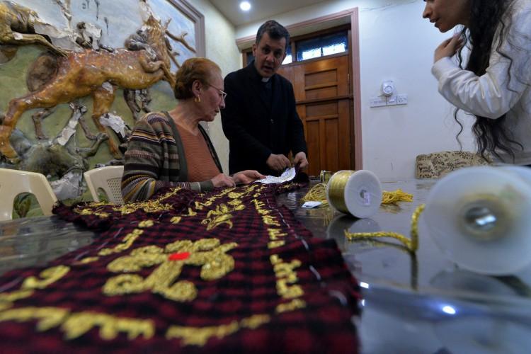 Sacerdote iraquiano Ammar Yaqo observa Karjiya Baqtar bordar um precioso xale de oração usando fio de ouro, para presentear o Papa Francisco  (Foto: Zaid AL-OBEIDI / AFP)